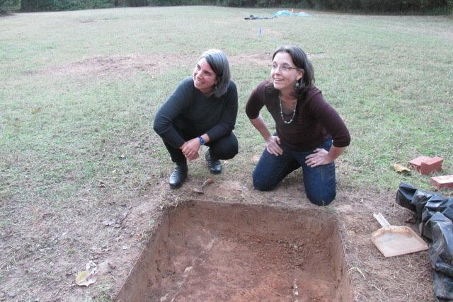 Jillian Galle (left) and Maureen Siewert Meyers check out an excavation unit outside of the Caroline Barr House at Rowan Oak.