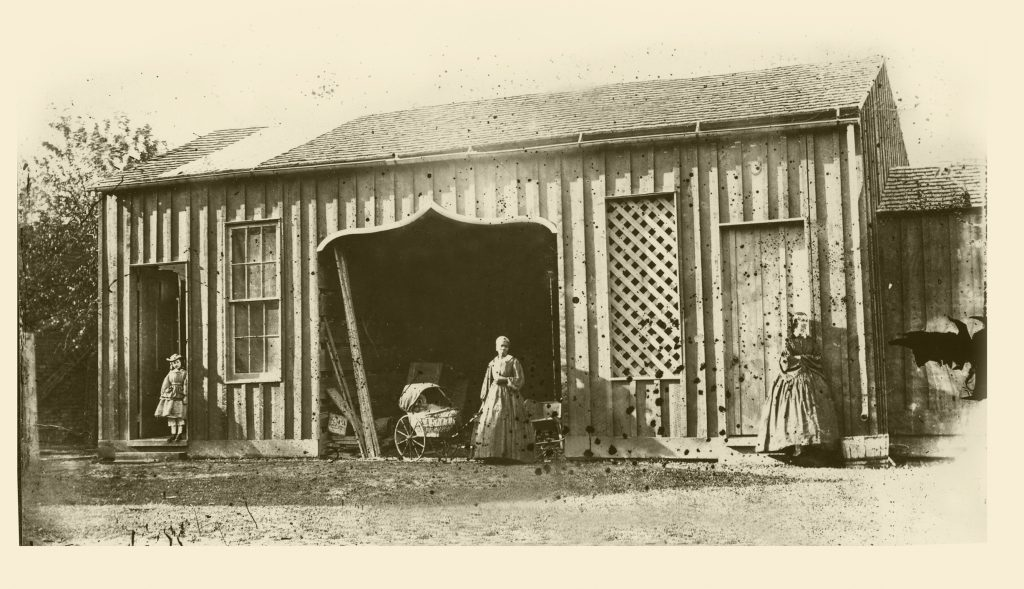 The University of Mississippi Carriage House and an (assumed) domestic servant, collodion glass plate negative by Edward C. Boynton, a professor of chemistry, minerology, and geology from 1856–1861. Courtesy of the University of Mississippi Department of Archives and Special Collections.